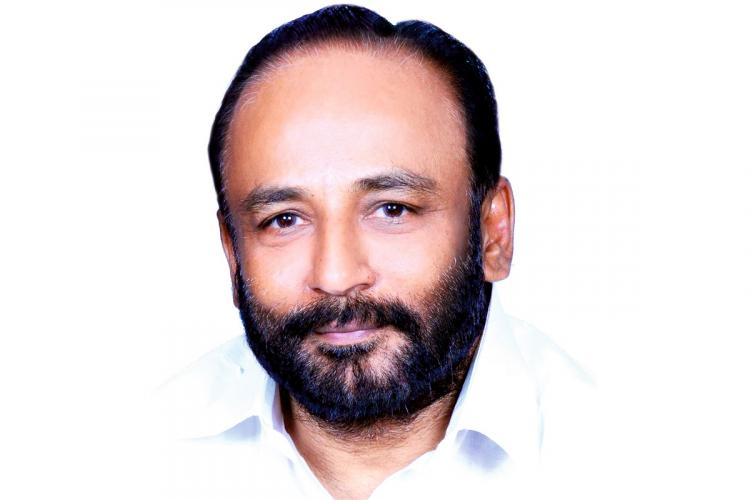 Gopinath with a beard and white shirt has a smiling expression on his face, the background is white