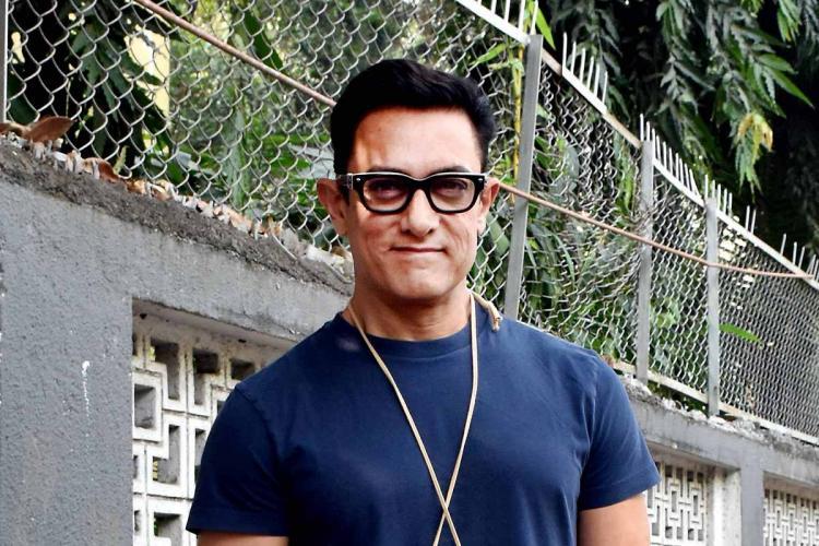 Actor Aamir Khan seen wearing a blue shirt and spectacles