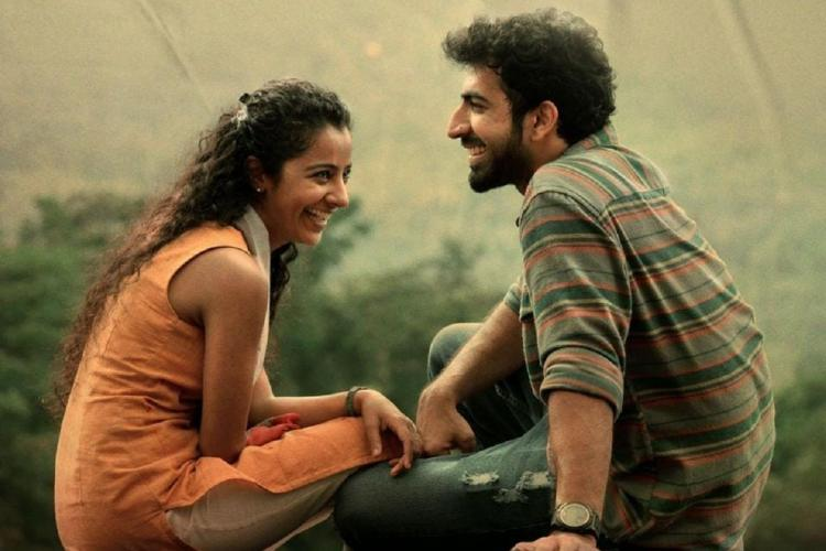 Darshana in a sleeveless peach kurthi sits sideways, laughing, facing Roshan Mathew who is also sitting sideways and laughing, wearing a shirt and jeans and has a beard
