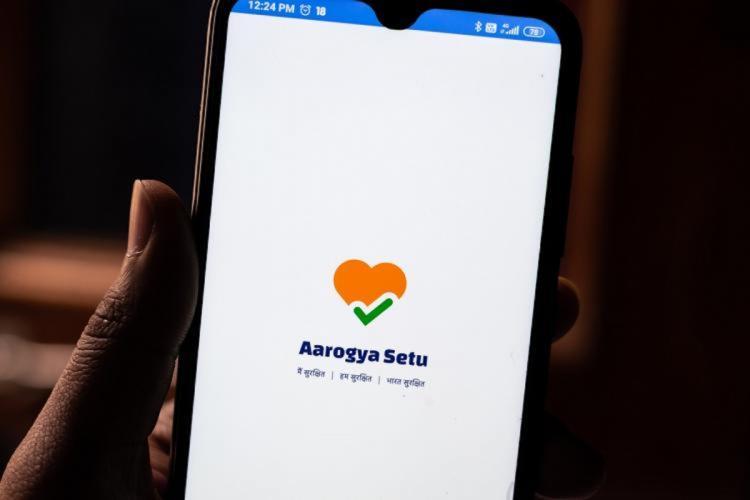 A hand holding a phone loading Aarogya Setu app