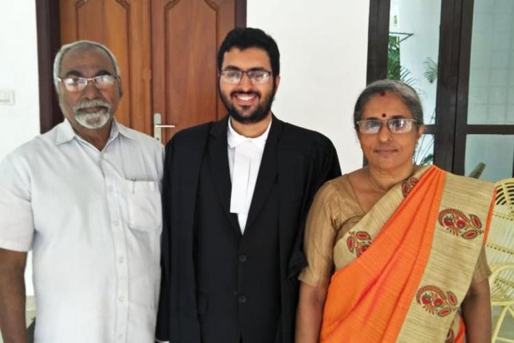 A young man in lawyer's coat stands between an older man dressed in white and a woman in an orange saree.
