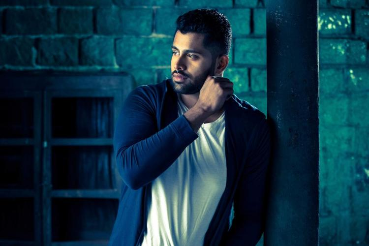 Sandalwood actor Abhishek Ambareesh posing in a dark blue jacket worn over a white t-shirt His right hand is raised to his left cheek and he is looking to his right