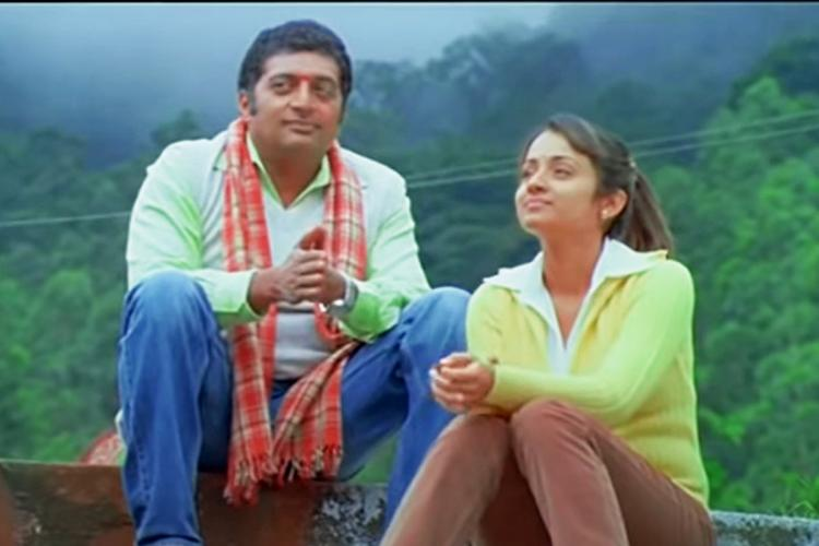 Trisha and Prakash Raj sitting on temple steps in Abhiyum Naanum
