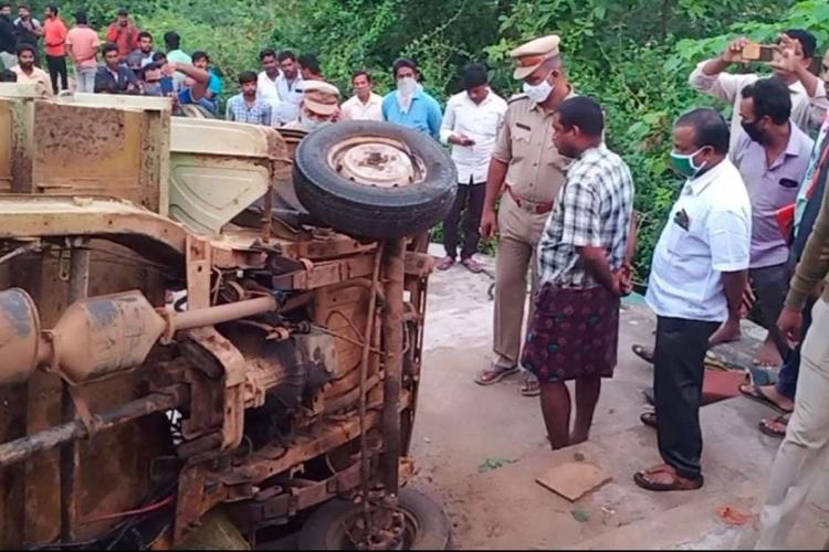 A van overturned and several other villagers including policemen in uniform were observing the vehicle