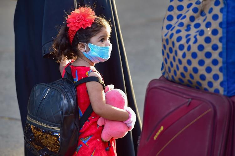 A child wearing a mask waits in a queue with her family members to board a special train.