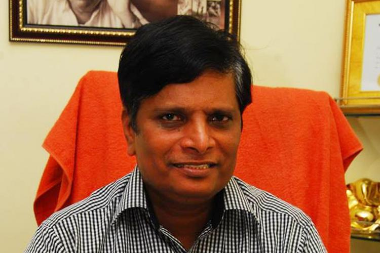 A file photo of child rights activist Achyuta Rao shows him seated on a chair behind a desk smiling at the camera