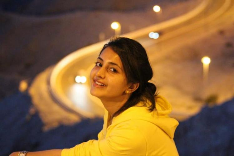 Actor Bhamaa in a yellow sweatshirt and hair tied up. She is seen smiling in this picture.