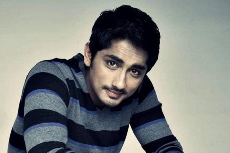 Actor Siddharth is smiling in this image. He is wearing a blue-black striped t-shirt.