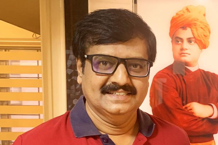 Actor vivek wearing a red shirt and standing in front of a poster of swami vivekananda
