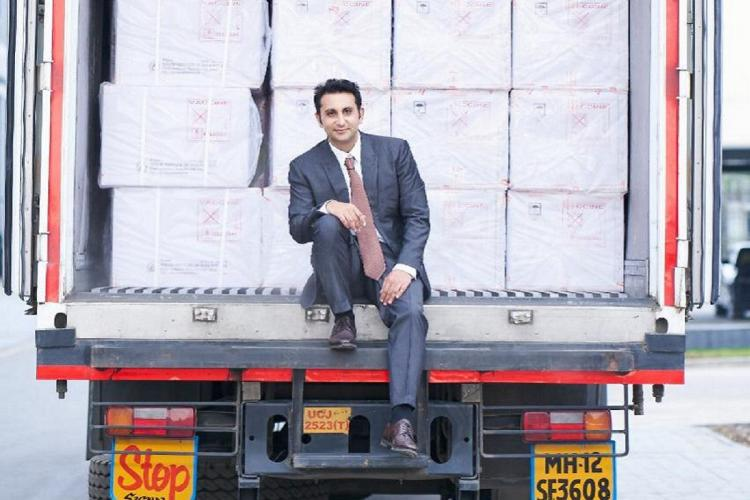 Adar Poonawalla sitting on a cargo truck with a shipment of vaccines behind him