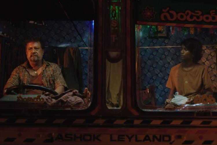 Screenshot from the series Addham where a man is driving a truck and a young boy is sitting next to him