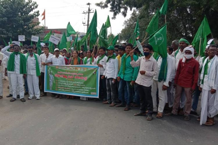 A group of protesters holding green flags and banners protesting against the Layout Registration Scheme in Telangana