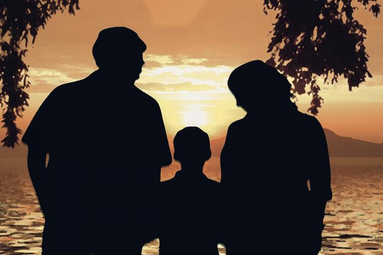 Silhouette of child with parents looking at the sea