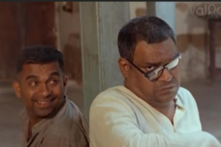 Brahmanandam and Kota Srinivasa Rao sitting with their backs against each other Kota Srinivasa Rao stares into the camera one side of his spectacles is broken Brahmanandam is looking at him and grinning