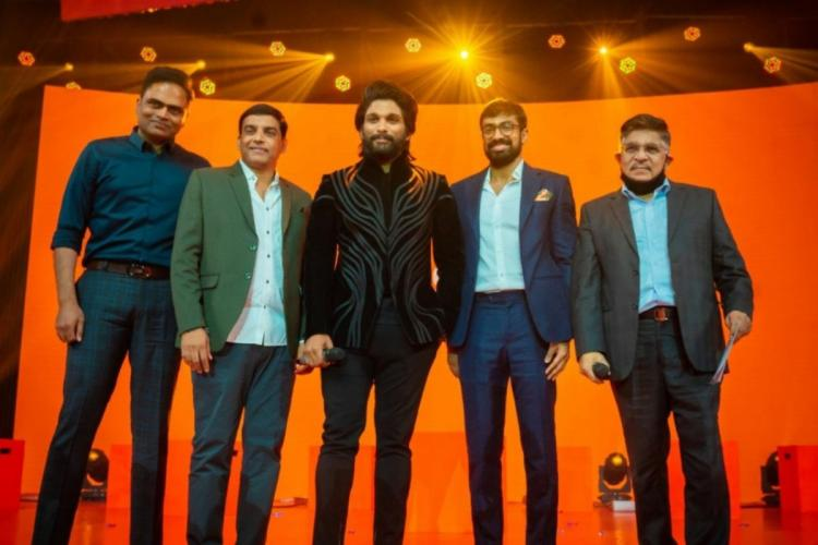 Actor Allu Arjun on the dais posing for photos along with Vamsi Paidipally Dil Raju against an orange background during Aha promotion event