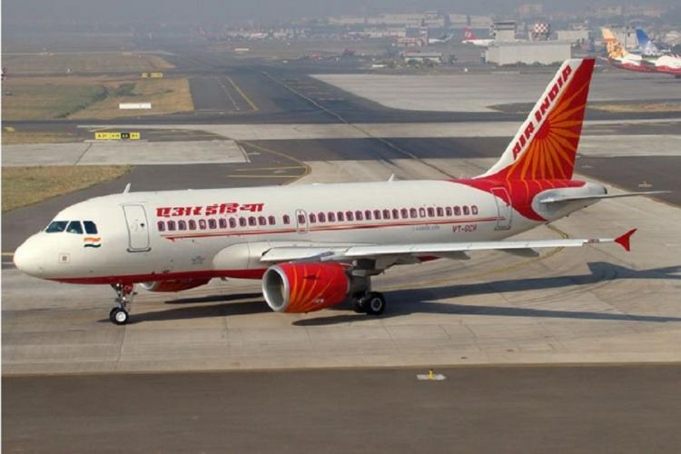 A white and red Air India flight getting ready for takeoff