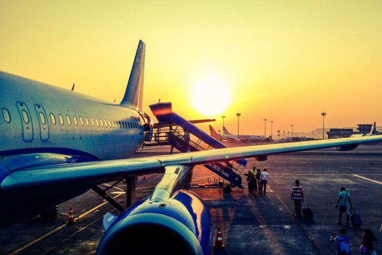 One side of an aircraft with a setting sun in the backdrop