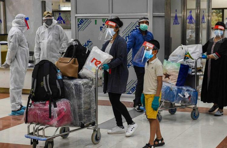 A woman and a child both wearing masks and a face shield pushing luggage at the airport
