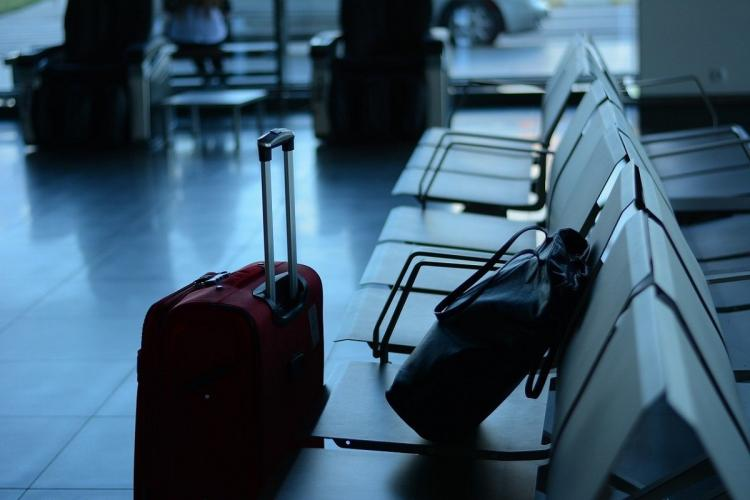 A suitcase and backpack on an airport seat