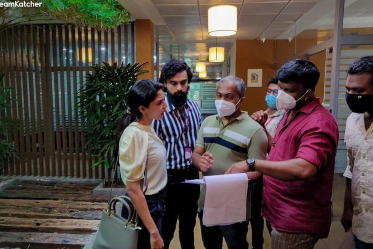 Aishwarya and Tovino listen to the director as the script is shown by someone in the crew