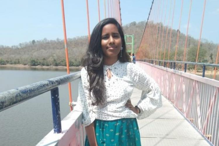 Aishwarya Reddy dressed in a green skirt and white top posing on a walkway over a river