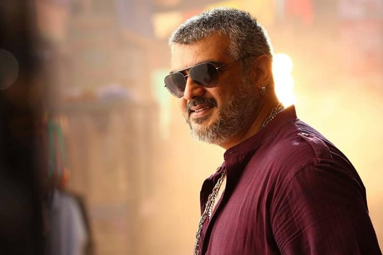 Actor Ajith wearing a maroon shirt and sunglasses smiling straight at the camera