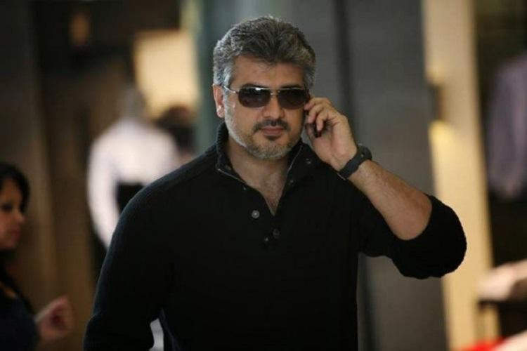 Ajith Kumar is seen wearing a black shirt and is seen speaking over phone in the image