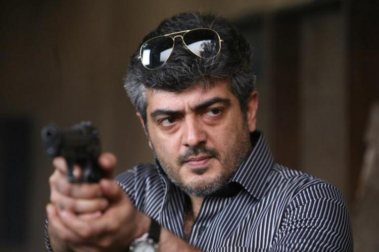 Ajith is pointing a gun in the image