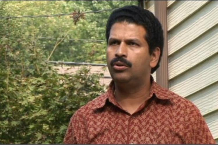 Josukutty as George is wearing a brick red shirt standing outside an apartment and in the background is a garden