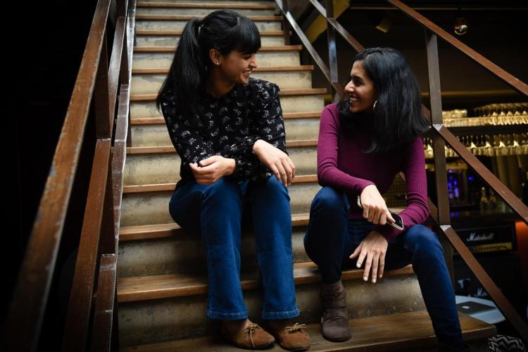 Aksha and Gouri sit on stairs looking at each other wearing their blue jeans and tops