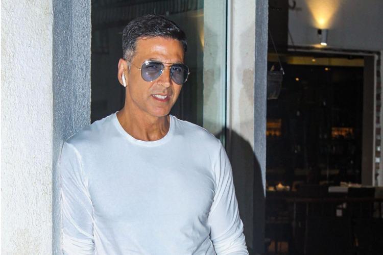Bollywood actor Akshay Kumar wearing a white shirt Airpods and sunglasses