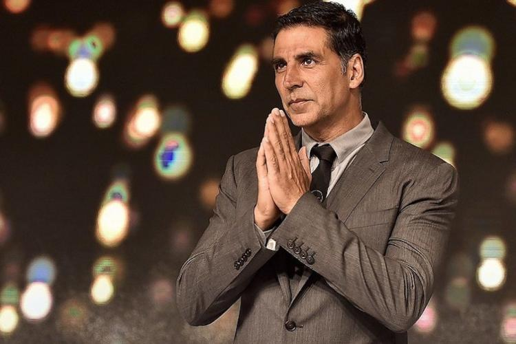Bollywood actor Akshay Kumar wearing a grey suit and folding his hands in a namaste