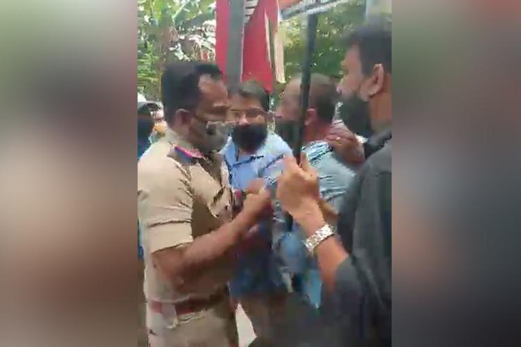 Police officer grabbing shirt of a parent protesting to reduce fees in a Kochi school