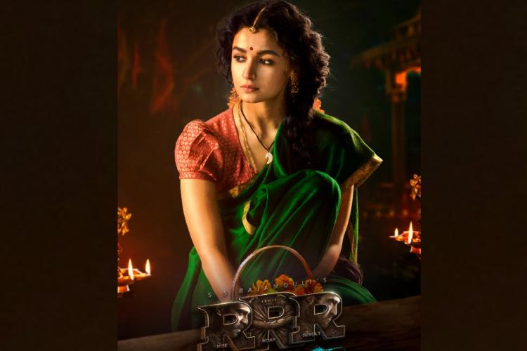 Alia Bhatt in a green saree sitting in a temple waiting for someone