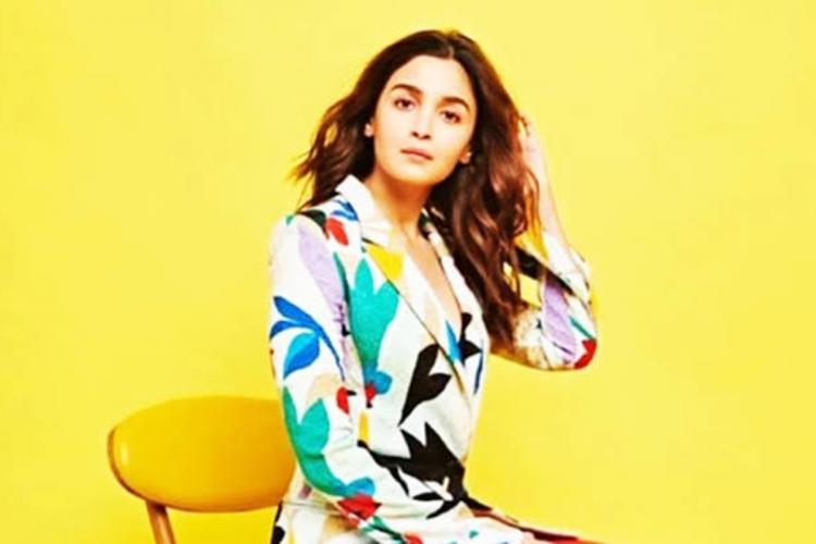 Alia Bhatt in a multicolour dress seated on a yellow chair against a yellow backdrop