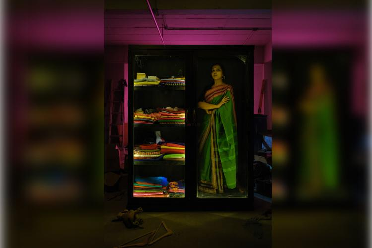 A woman stands inside an open almirah cupboard wearing a green saree with a red border with her hands folded On the other half of the almirah are stacked sarees and clothes The woman is depicting powerful as an emotion as part of The Almirah art project conceptutalised by Kochi-based fashion designer Sharmila Nair