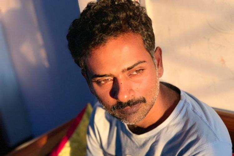 Alphonse Puthren looking away as day light falls on his face he is wearing a white t shirt and the shot is from above