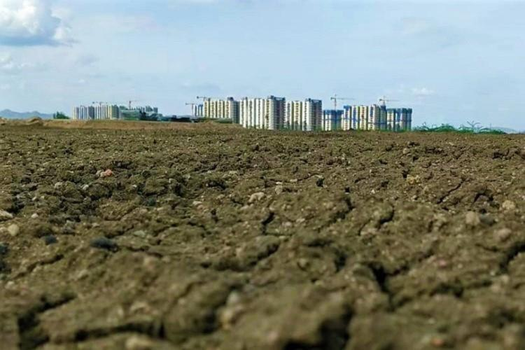 Cracked dried ground in Amaravati with concrete building in the distance