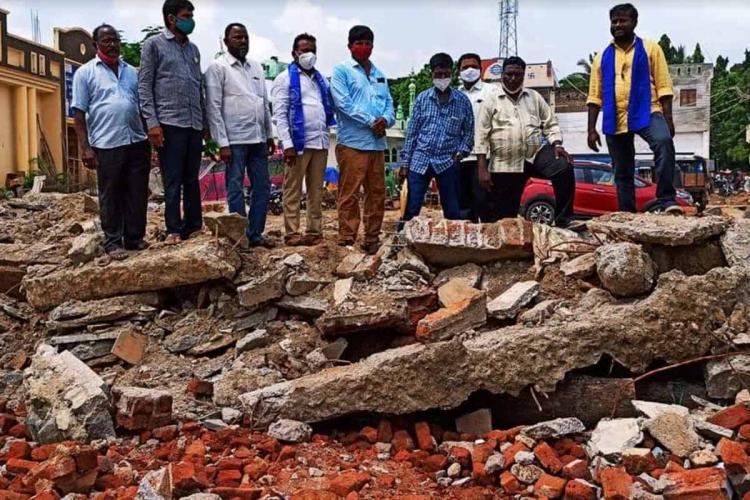 A group of men stand before debris following the demolition of the Ambedkar Bhavan in Telanganas Dornakal