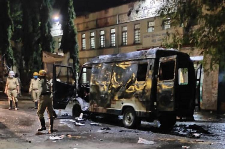 Charred remains of an ambulance of BIMS hospital in Belagavi in Karnataka, with three police officers standing near it