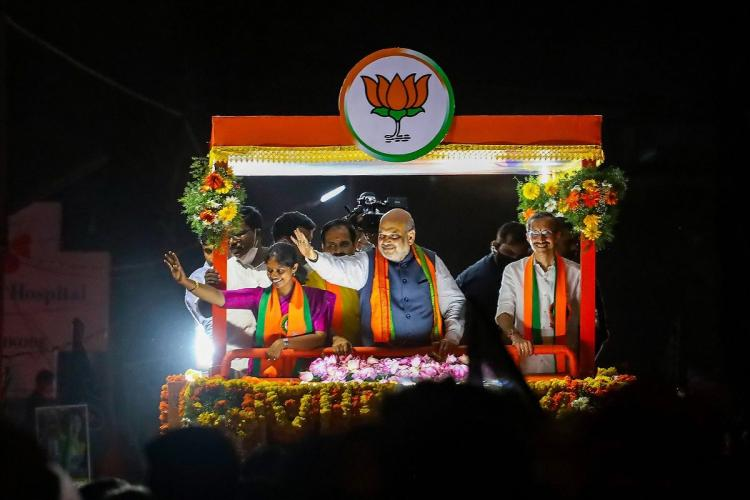 Amit Shah and a few others in a vehicle rally in the night, waving