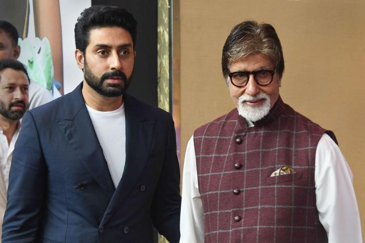 Bollywood actors Amitabh Bachchan and Abhishek Bachchan at an event in Mumbai. Abhishek wears a navy suit while Amitabh is dressed in a brown checkered Nehru jacket
