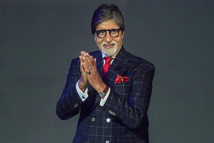 Amitabh Bachchan at an event wearing a checkered suit with a red pocket square and thick rimmed glasses with his head turned slightly towards his right