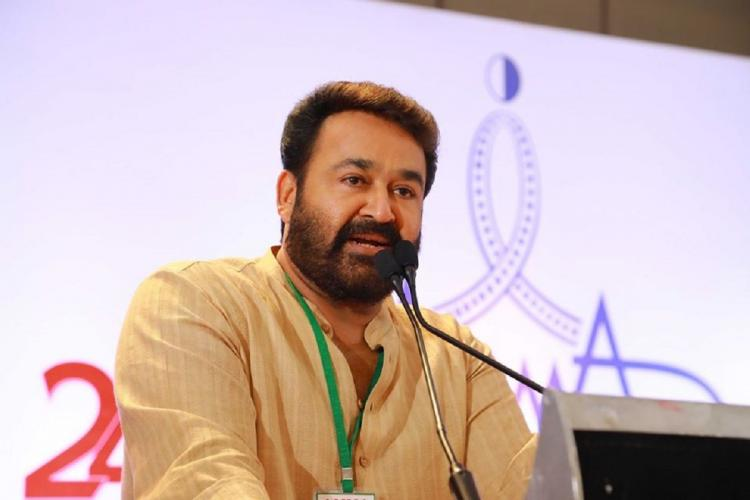 Beared Mohanlal stands before a microphone against a white screen in the background wearing a light coloured kurtha and a green tag and speaking