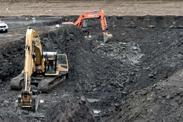 Two earth movers digging into an open cast coal mine