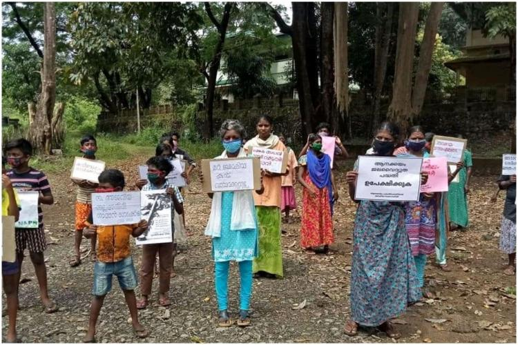 Tribal people holding placards to protest cutting off tress at Anakkayam Kerala