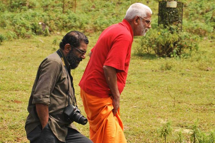 Anandatheertha Swami wearing a saffron dhoti with a red shirt is seen walking with journalist and filmmaker OK Johnny who is a dark grey and black trousers with a digital camera hanging from his neck