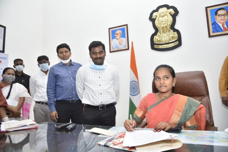Intermediate student Sravani wearing a pink saree seated in the collector's chair while the collector and other officials stand by