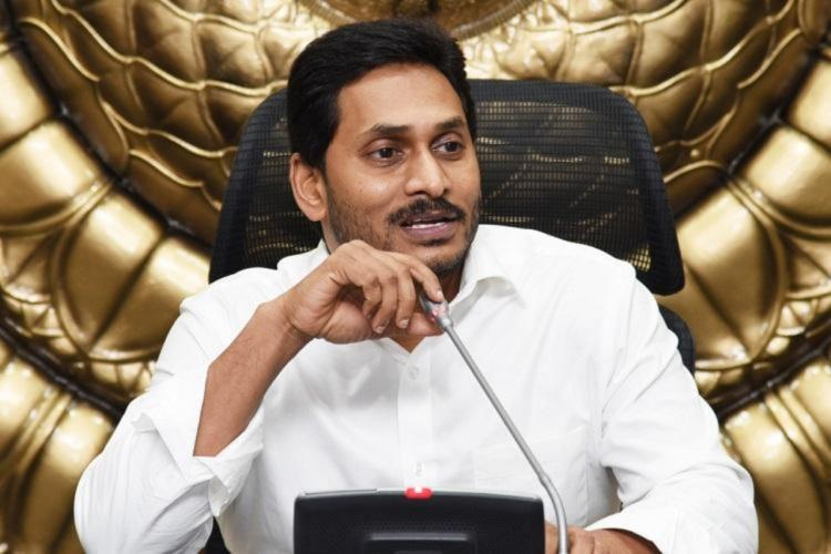 Andhra Pradesh Chief Minister Jagan Mohan Reddy in a white shirt sitting and speaking into a mic in front of him
