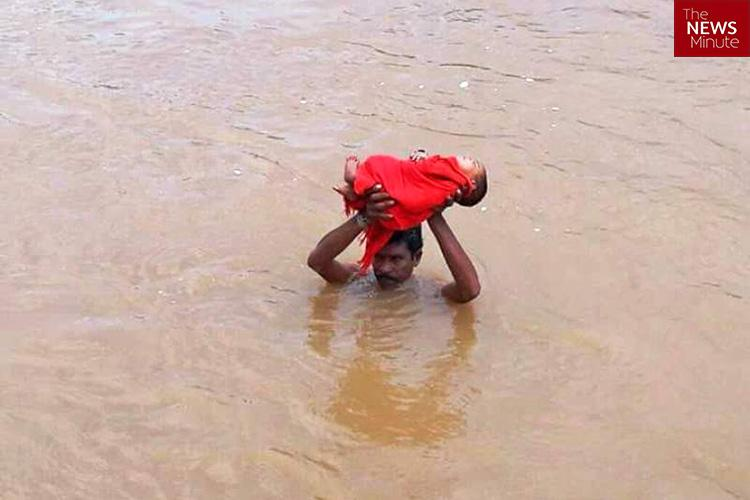 Andhra man wades through shoulder-level water carrying sick kid to hospital